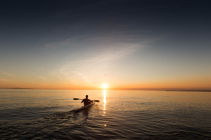 A person in a kayak in the sunset